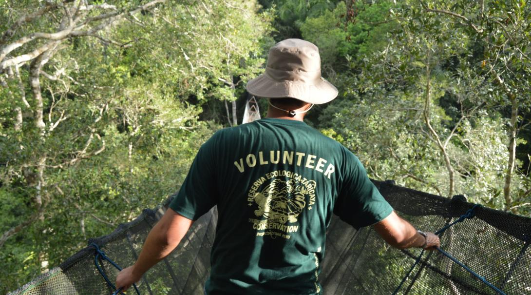 A Projects Abroad older volunteer participates in a wildlife survey in Peru from the tallest canopy walkway in South America.